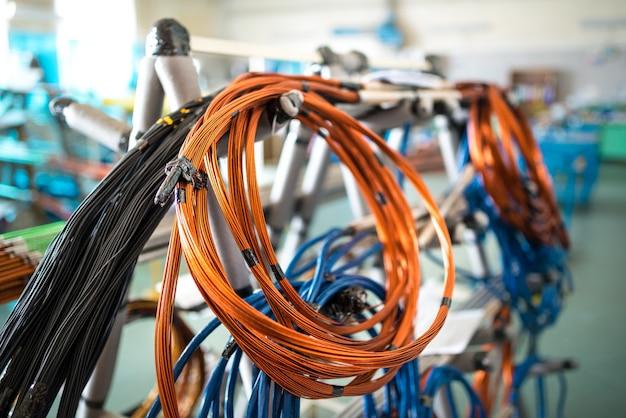 Cewka drutu miedzianego wisi na żelaznym stojaku przy produkcji sprzętu agd i artykułów elektrycznych. koncepcja dużej produkcji przemysłowej