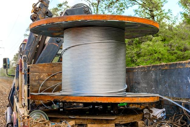 Cewka z kablem wysokiego napięcia zamontowana na wózku kołowym. montaż kabla na wspornikach wysokiego napięcia