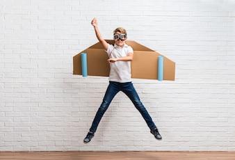 Chłopiec bawić się z kartonowymi samolotów skrzydłami skacze