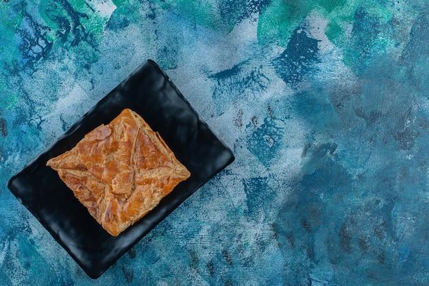 Chaczapuri ułożone warstwowo na drewnianym talerzu, na marmurowym stole.