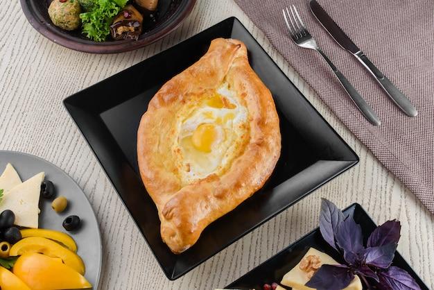 Chaczapuri z serem i pomidorami, jajko, plastry warzyw, bazylia na białym drewnianym stole. porcja. widok z góry.