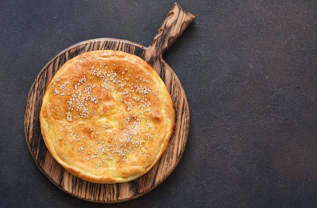Chaczapuri z serem suluguni i serem na drewnianej desce. widok svehu.