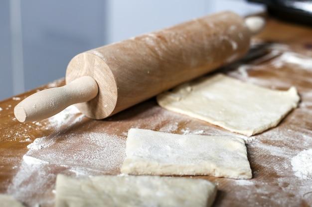 Chaczapuri z serem w środku na drewnianym tle mąka bułka ciasto ser gotowanie chaczapuri ciasto mączne i wałek na stole ciasto francuskie