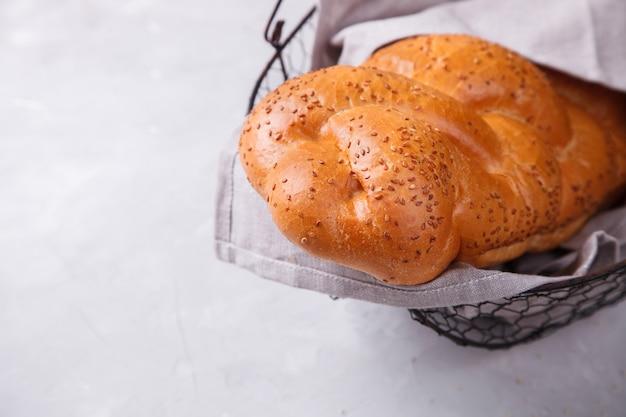Chałka chleba z sezamem, w metalowym koszu