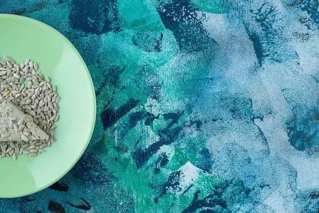 Chałwa słonecznikowa w plasterkach z pestkami na talerzu, na marmurowym stole.