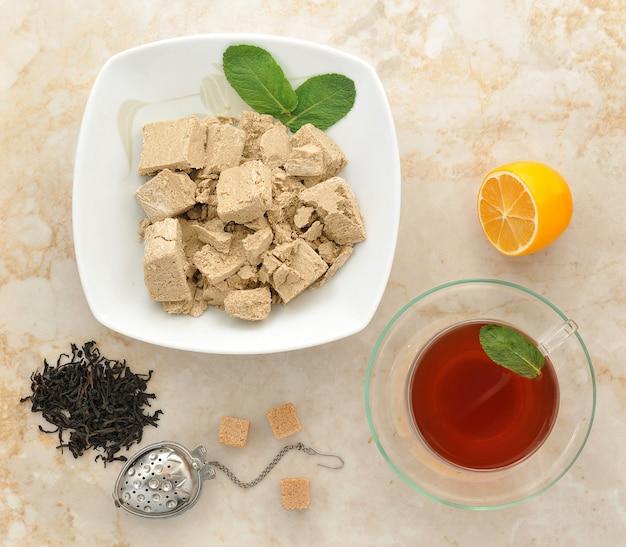 Chałwa w talerzu z liśćmi mięty, czarna herbata w przezroczystym kubku z miętą, łyżką i kostkami cukru na marmurowej powierzchni
