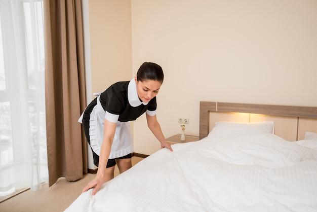 Chambermaid przygotowuje pokój hotelowy