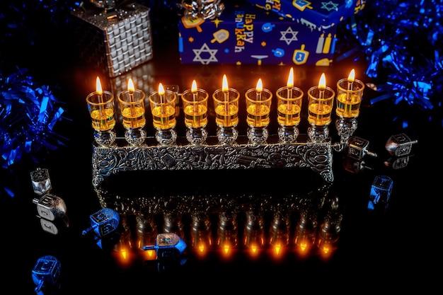 Chanukowa menora z płonącymi świecami olejowymi i pudełkami na prezenty. święto żydowskie.