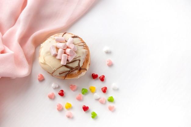 Chanukowy pączek i kolorowe cukierki na białym stole