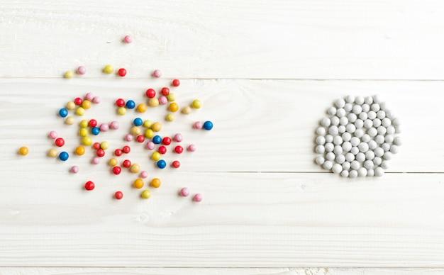 Chaotyczne kolorowe kule i zorganizowane białe kule. konceptualny obraz porządku i chaosu
