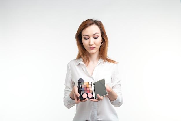 Charakteryzator, uroda i koncepcja ludzi - piękna koreańska młoda kobieta trzyma paletę kolorowych cieni do powiek i pędzli