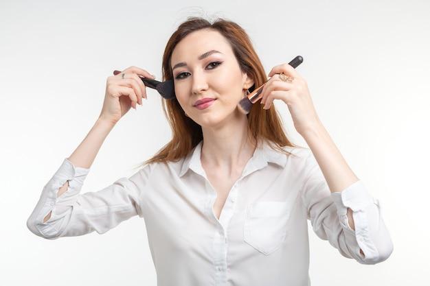 Charakteryzator, uroda i ludzie koncepcja - piękna koreańska młoda kobieta trzyma pędzle do makijażu na białej ścianie