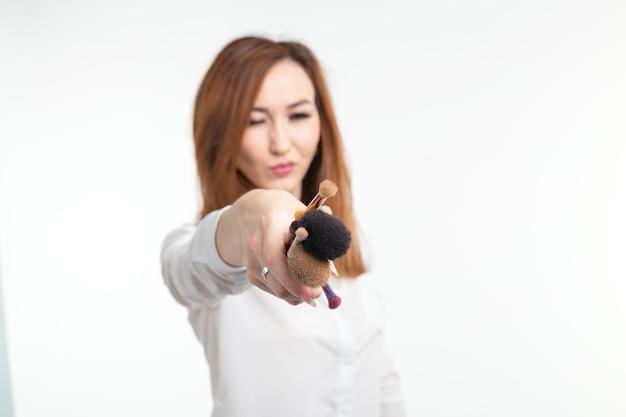 Charakteryzator, uroda i ludzie koncepcja - piękna koreańska młoda kobieta trzyma pędzle do makijażu