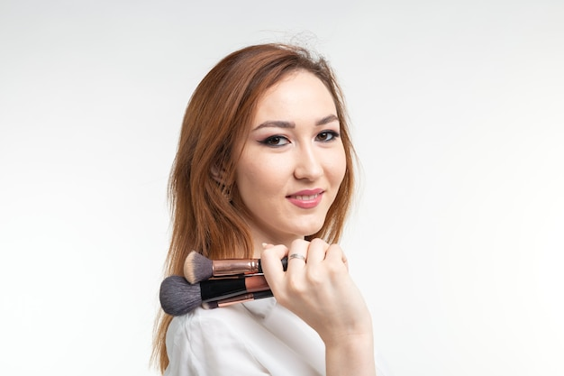 Charakteryzator, uroda i ludzie koncepcja - piękna koreańska młoda kobieta trzymając pędzle do makijażu