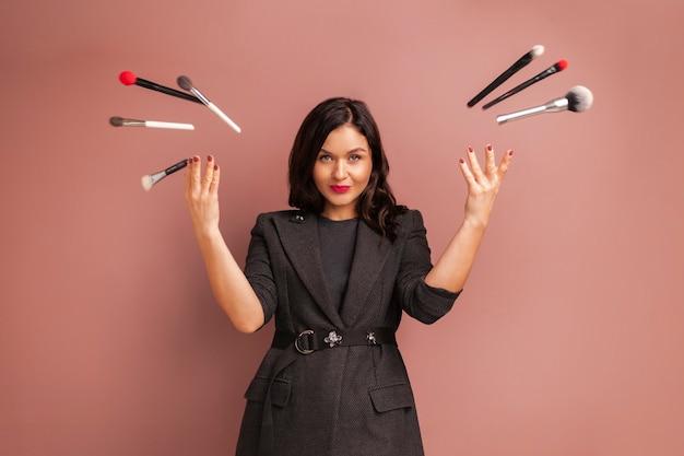 Charakteryzatorka kobieta uśmiecha się i rzuca w górę pędzle i narzędzia