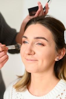 Charakteryzatorka profesjonalnego makijażu uśmiechnięta młoda kobieta lekcje makijażu