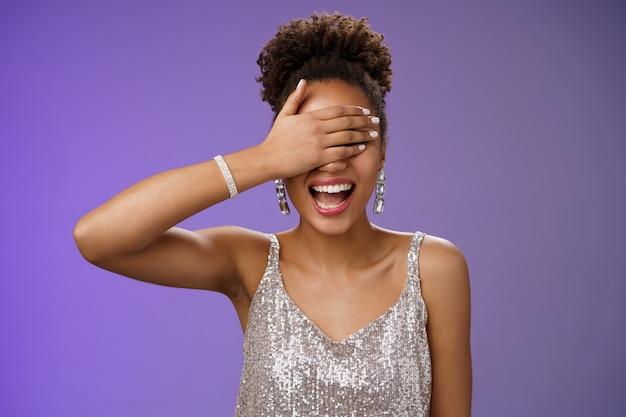 Charyzmatyczna afrykańska dziewczyna w błyszczącej srebrnej sukni wieczorowej zamknij oczy palma uśmiechając się śmiejąc się szczęśliwie czekając na imprezę niespodziankę z okazji urodzin chce otrzymać prezent przewidujący w pobliżu niebieskiego tła.