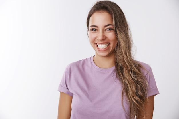 Charyzmatyczna beztroska atrakcyjna zdrowa kobieta śmiejąca się głośno uśmiechnięte białe zęby chichocząca zabawa, ciesząca się niesamowitym przyjaznym towarzystwem oglądając komedię, chichocząc śmieszny żart, biała ściana