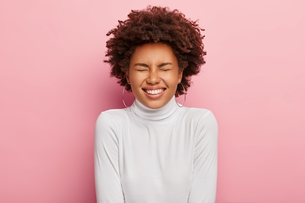 Charyzmatyczna beztroska kobieta śmieje się z przezabawnego żartu, zamyka oczy, pokazuje idealne zęby
