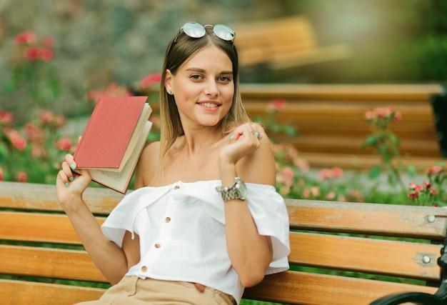 Charyzmatyczna kobieta w letnich ubraniach siedzi na ławce z książką