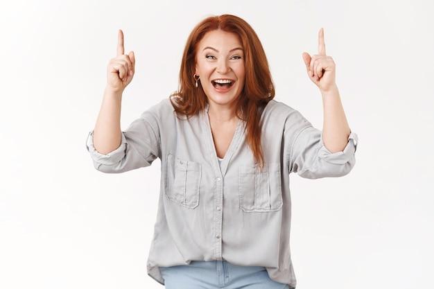 Charyzmatyczna przystojna szczęśliwa szczęśliwa rudowłosa kobieta w średnim wieku śmiejąca się rozbawiona radośnie chichocząca wskazująca podniesione ręce do góry niesamowite przezabawne ceny dobry promo wygląd aparat podekscytowany, biała ściana