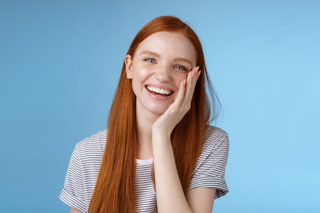 Charyzmatyczna rozmowna przyjazna wyglądająca wesoło roześmiana ruda dziewczyna dobrze się bawiąca omawianie poprzednich wakacji żartuje chichocząc wzruszająca twarz rozbawiona stojąca wesoła błękitne tło
