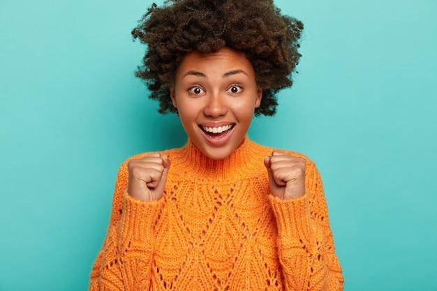 Charyzmatyczna urocza afroamerykanka wita zwycięstwo, podnosi zaciśnięte pięści, coś świętuje, uśmiecha się szeroko, pokazuje białe zęby, nosi dzianinowy pomarańczowy sweter