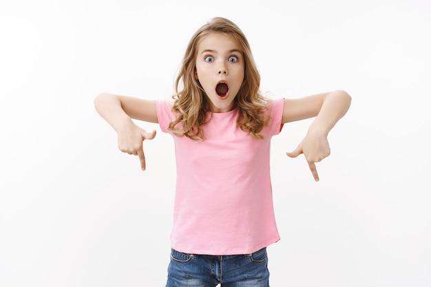 Charyzmatyczna zdumiona urocza blond europejska dziewczyna w różowej koszulce, wyjaśnia niesamowitą rzecz, wygląda na zdziwioną i podekscytowaną, otwarte usta krzyczą pod wrażeniem, wskazuje w dół, wskazuje dolną promo