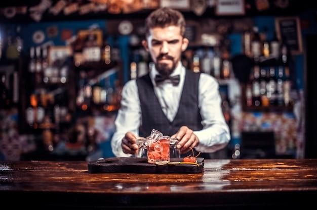 Charyzmatyczny barman tworzy show tworząc koktajl w nocnym klubie