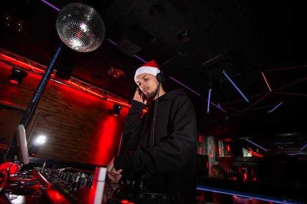 Charyzmatyczny disc jockey w czerwonej czapce świętego mikołaja, słuchawkach i kapturze odtwarza muzykę na gramofonach dj-skich. przyjęcie bożonarodzeniowe