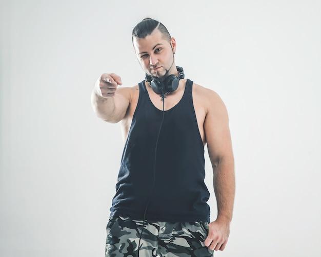 Charyzmatyczny dj - raper ze słuchawkami na białej ścianie. na zdjęciu jest puste miejsce na twój tekst