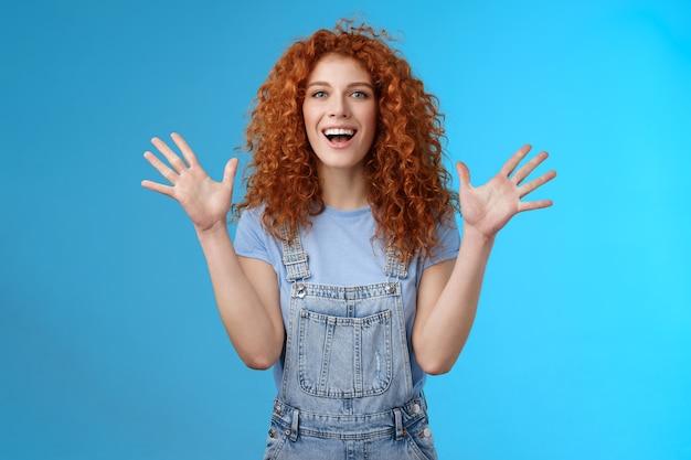 Charyzmatyczny jasny szczęśliwy rozbawiony ruda przystojny letni imbir dziewczyna podnieść ręce zachwycony doping pochlebiony uśmiechający się szeroko biały uśmiech ząb wyraża szczęście radość tło studio.