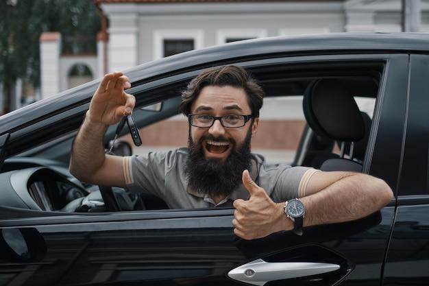 Charyzmatyczny mężczyzna trzyma kluczyki do samochodu pokazując kciuk do góry