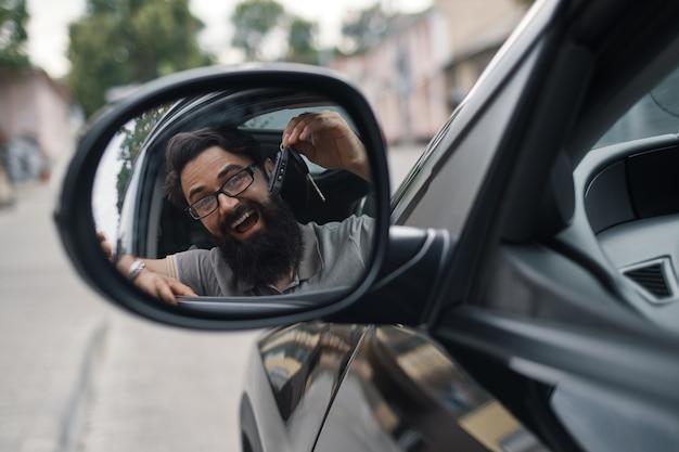 Charyzmatyczny mężczyzna trzyma kluczyki do samochodu