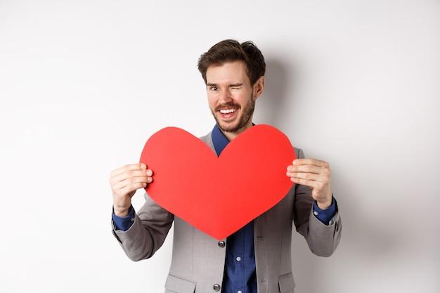 Charyzmatyczny młody człowiek mrugający i uśmiechnięty, pokazujący duże czerwone serce na randkę w walentynki, mówi kocham cię kochankowi, stojąc na białym tle.