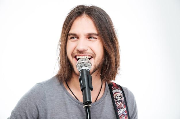 Charyzmatyczny pozytywny młody człowiek śpiewający do mikrofonu i grający na gitarze na białym tle