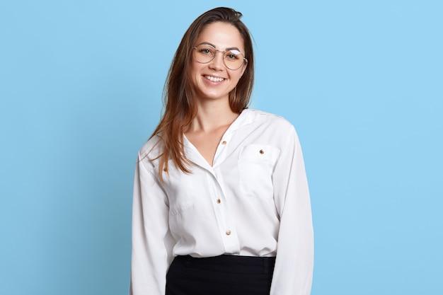Charyzmatyczny przystojny model ubrany w czarną spódnicę, białą bluzkę i okulary.