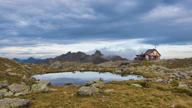Chata alpejska w pobliżu małego górskiego jeziora