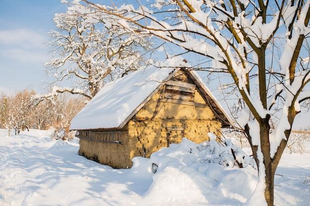 Chata w polu pokrytym śniegiem w promieniach słońca w zimie