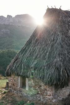 Chata we wsi la peral ze słońcem w tle.
