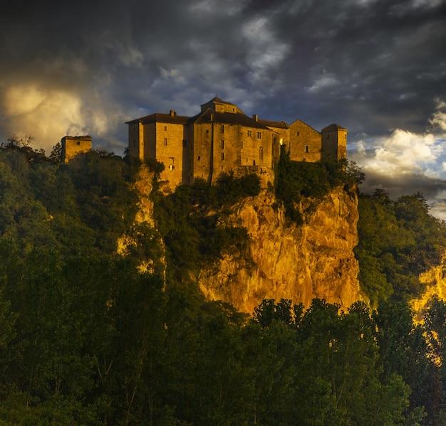 Chateau de bruniquel otoczony zielenią i skałami pod zachmurzonym niebem podczas zachodu słońca we francji