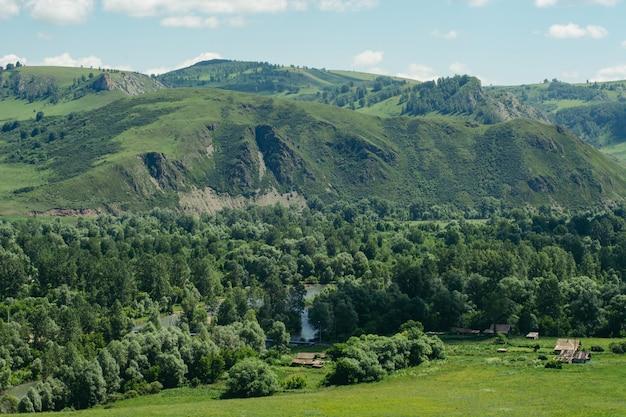Chaty zbudowane wśród gór i wzgórz. wieś ałtaj, rosja. krajobraz.