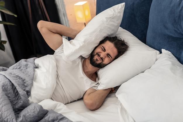 Chcę ciszy. nieszczęśliwy, niewesoły mężczyzna zakrywający uszy, gdy chce spać