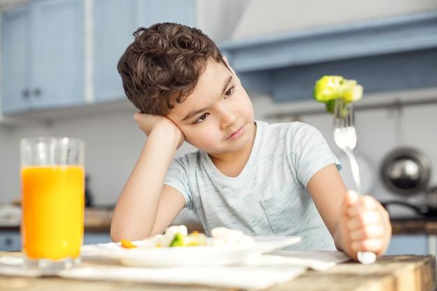 Chcę cukierki. przystojny, smutny, ciemnowłosy chłopiec ma zdrowe śniadanie i patrzy na zielone warzywo na widelcu i nie lubi tego