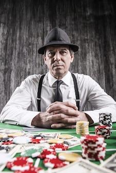 Chce grać? poważny starszy mężczyzna w koszuli i szelkach siedzący przy stole pokerowym i patrzący w kamerę z kartami z pieniędzmi i żetonami do gry leżącymi wokół niego
