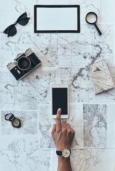 Chcę odwiedzić każde miejsce. widok z góry na człowieka za pomocą smartfona