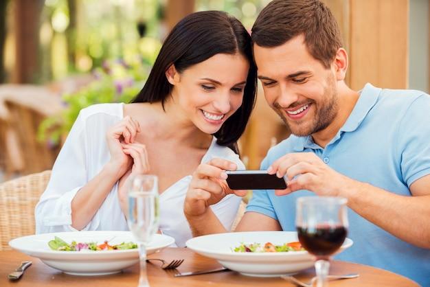 Chcę podzielić się tym zdjęciem z przyjaciółmi. szczęśliwa młoda kochająca para robi zdjęcia jedzenia i uśmiecha się podczas wspólnego relaksu w restauracji na świeżym powietrzu
