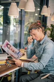 Chcę spać. miły, zmęczony mężczyzna przecierający oczy czytając czasopismo naukowe
