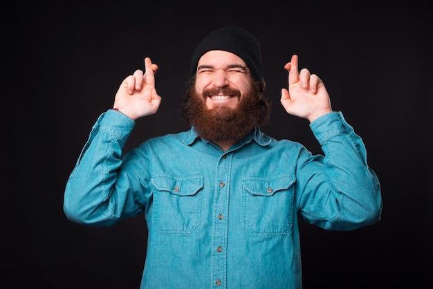 Chcę to. wesoły brodaty mężczyzna hipster ze skrzyżowanymi palcami marzy