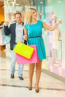 Chcę to wszystko! pełna długość dojrzałej pary robi zakupy razem w centrum handlowym, podczas gdy kobieta wskazuje manekin